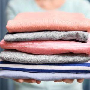 depositphotos_130399042-stock-photo-woman-holding-folded-clothes